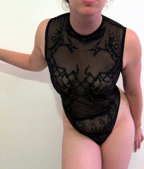 The author Liz wearing a sheer black bodysuit with detailed lattice and snake embroidery by designer Erica M.