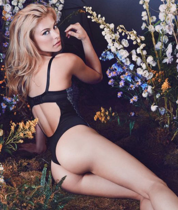 A woman in front of a floral backdrop wearing a thong bodysuit in nightshade by designer Fortnight Lingerie.