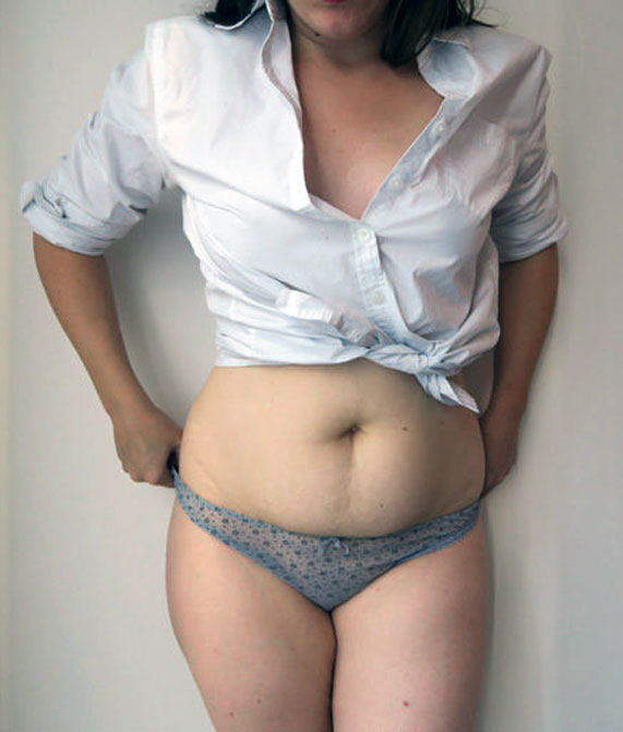 The author Liz wearing a white button down shirt tied above her stomach and a grey thong with flowers by designer Intimissi.