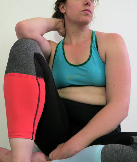 The author Liz wearing a blue sports bra and leggings colourblocked black, grey, orange and blue.