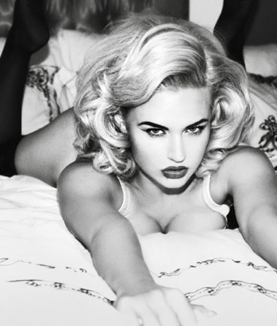 A black and white photo of a model on a bed wearing Playful Promises lingerie.