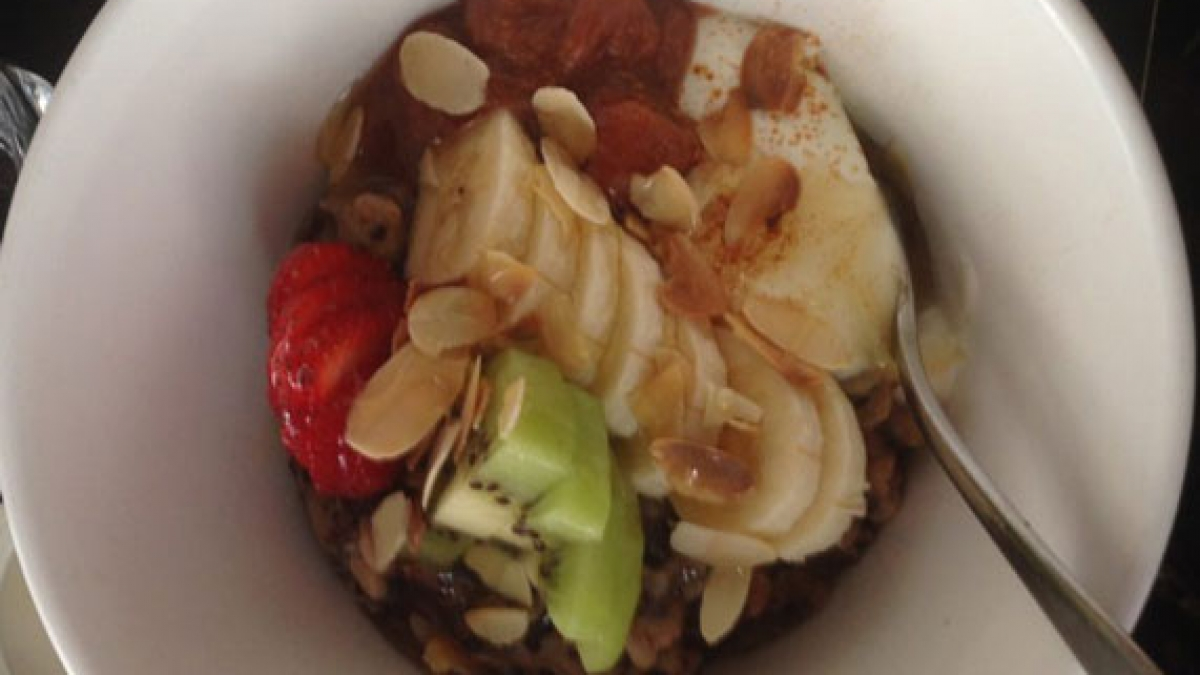 A bowl of bircher museli with kiwi, banana and other fruit and nuts.