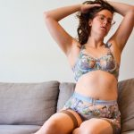 Liz looks to the camera wearing a bust-boosting Botanica set in dusty blue, where the lace is embellished with green and blue plant motifs and a peek-a-boo centre to the bra.