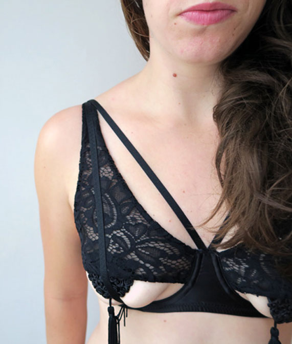 The author Liz wearing a black lace strappy bra with an open bottom cup and pasties on her nipples by designer Peek and Beau.
