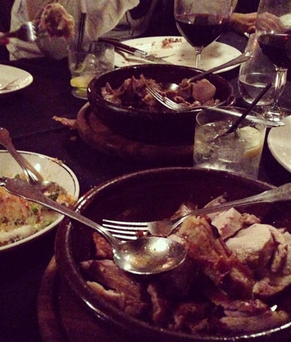 A restaurant table with multiple meat dishes.
